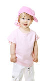 Cute baby girl in a pink cap looks into the camera Stock Images