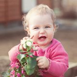 Cute baby girl in pink dress puts flowers Royalty Free Stock Image