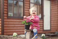 Cute baby girl in pink dress puts flowers Stock Photo