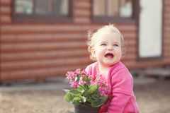 Cute baby girl in pink dress puts flowers Royalty Free Stock Photo