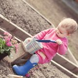 Cute baby girl in pink dress puts flowers Stock Photos