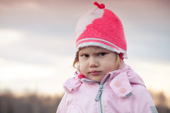 Cute baby girl in pink hat angry frowns Stock Photos