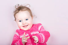 Cute baby girl in a pink knitted sweater with hearts pattern. On a pink blanket Royalty Free Stock Photos