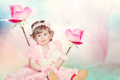 Cute baby girl on pink roses background Royalty Free Stock Images
