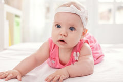 Cute baby girl in pink with white tie Stock Photo