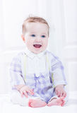 Cute baby girl in plaid purple dress sitting in white nursery Royalty Free Stock Photos