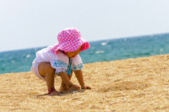 Cute baby girl playing on the beach Royalty Free Stock Photos