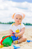 Cute baby girl playing on the beach with sand. Stock Photography
