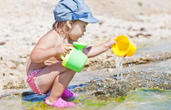 Cute baby girl playing on the beach Stock Photography