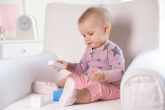 Cute baby girl playing with building blocks in armchair. At home stock photography