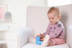 Cute baby girl playing with building blocks in armchair at home. Space for text stock photo