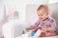 Cute baby girl playing with building blocks in armchair at home. Space for text stock photography