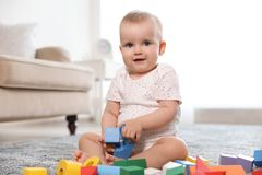 Cute baby girl playing with building blocks. In room stock photo
