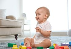 Cute baby girl playing with building blocks. In room stock images