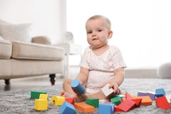 Cute baby girl playing with building blocks. In room royalty free stock image