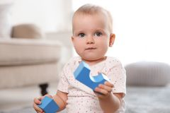 Cute baby girl playing with building blocks. In room royalty free stock photos