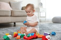 Cute baby girl playing with building blocks. In room stock image