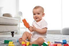 Cute baby girl playing with building blocks. In room stock photography