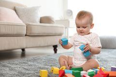 Cute baby girl playing with building blocks in room. Space for text royalty free stock photos