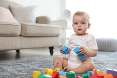 Cute baby girl playing with building blocks in room. Space for text royalty free stock photo