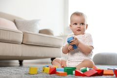 Cute baby girl playing with building blocks. Space for text. Cute baby girl playing with building blocks in room. Space for text stock image