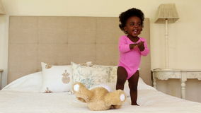 Cute baby girl playing and clapping on bed