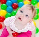 Cute baby girl playing among colorful balls Royalty Free Stock Photography