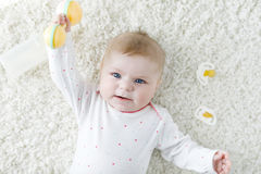 Cute baby girl playing with colorful pastel vintage rattle toy. Cute adorable newborn baby playing with colorful pastel vintage rattle toy. New born child Stock Photo