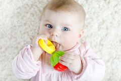 Cute baby girl playing with colorful pastel vintage rattle toy Stock Photos