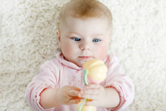 Cute baby girl playing with colorful pastel vintage rattle toy. Cute adorable newborn baby playing with colorful pastel vintage rattle toy. New born child Royalty Free Stock Photos