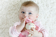 Cute baby girl playing with colorful pastel vintage rattle toy. Cute adorable newborn baby playing with colorful pastel plush bunny toy. New born child, little Royalty Free Stock Image