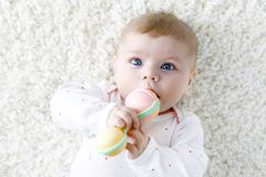 Cute baby girl playing with colorful pastel vintage rattle toy. Cute adorable newborn baby playing with colorful pastel vintage rattle toy. New born child Royalty Free Stock Photography