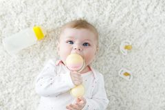 Cute baby girl playing with colorful pastel vintage rattle toy. Cute adorable newborn baby playing with colorful pastel vintage rattle toy. New born child Stock Images