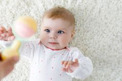 Cute baby girl playing with colorful pastel vintage rattle toy. Cute adorable newborn baby playing with colorful pastel vintage rattle toy. New born child Stock Photos
