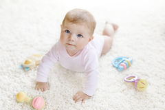 Cute baby girl playing with colorful pastel vintage rattle toy. Cute baby playing with colorful pastel vintage rattle toy. New born child, little girl looking at Royalty Free Stock Images
