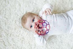 Cute baby girl playing with colorful rattle toy royalty free stock images