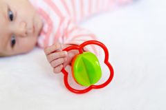Cute baby girl playing with colorful rattle toy Stock Photos