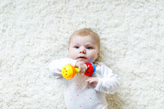 Cute baby girl playing with colorful rattle toy. Cute adorable newborn baby playing with colorful rattle toy on white background. New born child, little girl Royalty Free Stock Image