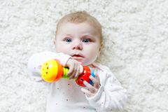 Cute baby girl playing with colorful rattle toy. Cute adorable newborn baby playing with colorful rattle toy on white background. New born child, little girl Stock Photography