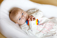 Cute baby girl playing with colorful rattle toy Stock Images