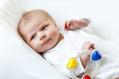 Cute baby girl playing with colorful rattle toy Royalty Free Stock Photos
