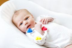Cute baby girl playing with colorful rattle toy. Cute adorable newborn baby playing with colorful rattle toy. in white bed at home. New born child, little girl Royalty Free Stock Photo