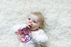 Cute baby girl playing with colorful rattle toy. Cute adorable newborn baby playing with colorful ball toy on white background. New born child, little girl Stock Images