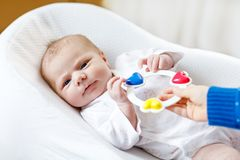 Cute baby girl playing with colorful rattle toy. Cute adorable newborn baby playing with colorful rattle toy. in white bed at home. New born child, little girl Stock Image