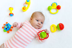 Cute baby girl playing with colorful rattle toys Royalty Free Stock Photos