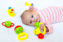 Cute baby girl playing with colorful rattle toys Royalty Free Stock Photo