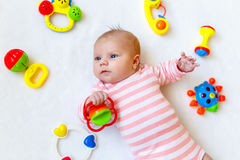 Cute baby girl playing with colorful rattle toys Stock Photos