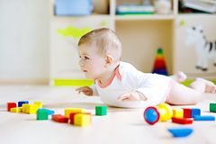 Cute baby girl playing with colorful rattle toys Stock Photography