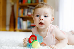 Cute baby girl playing with colorful rattle toys. Cute happy smiling baby playing with colorful rattle toys. New born child, little girl looking at the camera royalty free stock photo