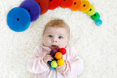 Cute baby girl playing with colorful wooden rattle toy. Cute adorable newborn baby playing with colorful wooden rattle toy ball on white background. New born Royalty Free Stock Image